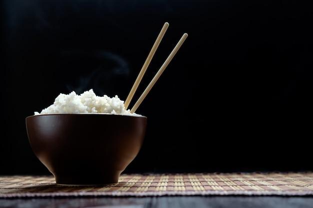 Hete rijst in bruine kom met stokjes in japanse stijl