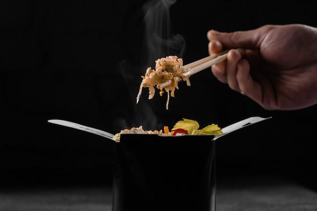 Hete rijst in wokdoos op zwarte oppervlakte stomen