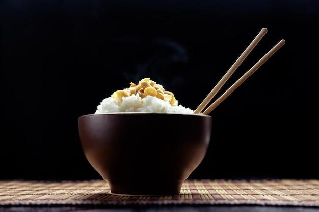 Hete rijst met natto in bruine kom met eetstokjes in japanse stijl