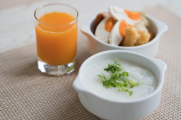 Hete rijstbrij die met jus d'orange voor ontbijt wordt geplaatst
