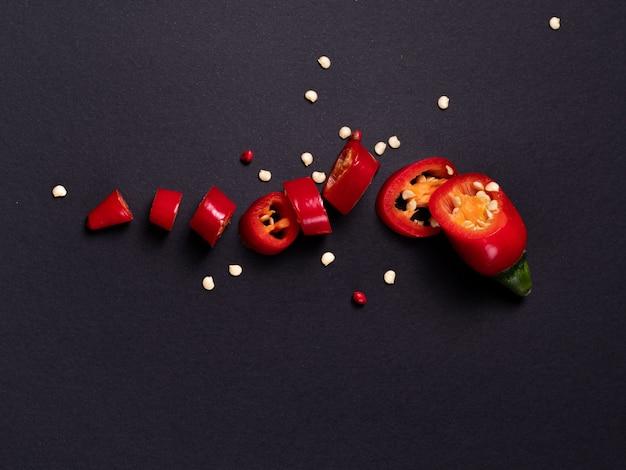 Hete rode chilipeper ligt op een zwarte tafel, een kleine peul die in veel stukken is gesneden. thuis koken.