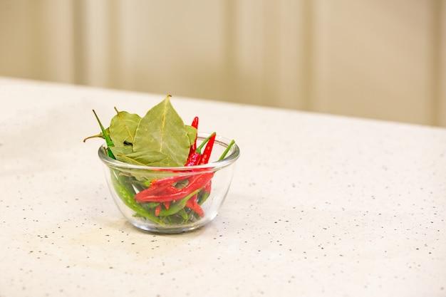 Hete rode en groene paprika's met kruiden in een kom voor smakelijke chilisaus in kom