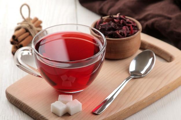 Hete rode karkade thee in glazen bekers met droge thee op een witte houten tafel
