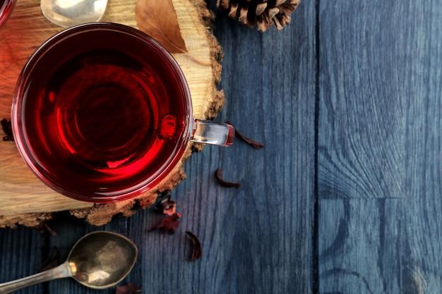 Hete rode karkadethee in glazen beker op een houten standaard op een donkerblauwe tafel