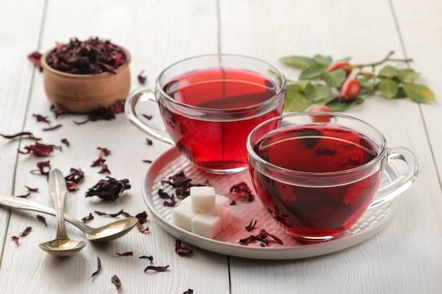 Hete rode karkadethee in kopjes met droge thee op een witte houten lijst