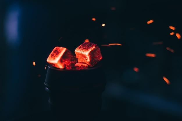 Hete rode kolen met waterpijp vonken in metalen kom voor shisha roken en traditionele aziatische ontspanning