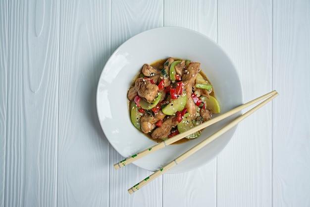 Hete salade met kip, courgette en chili, sesamzaadjes en kruiden.