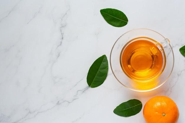 Hete sinaasappelthee en verse sinaasappel op tafel