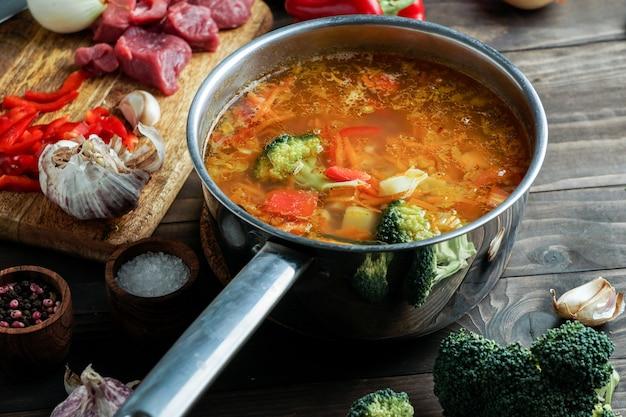 Hete soep in een pan is aan het stomen. met rundvlees en groenten. stevig, voedzaam gerecht. diner