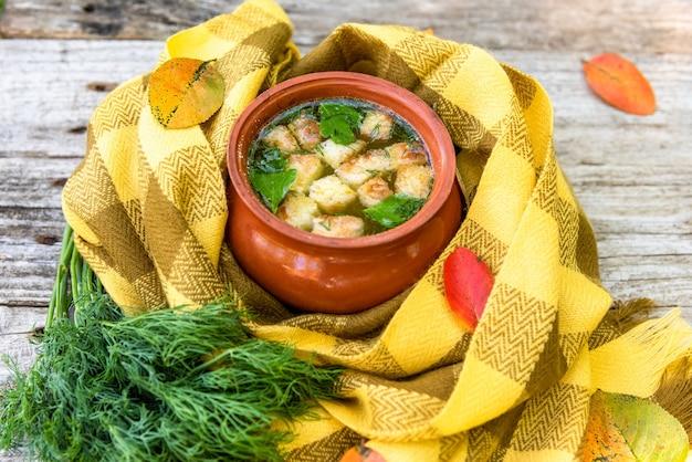 Hete soep met croutons in een aarden pot.