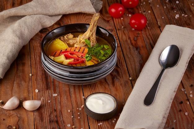 Hete soep met lamsvlees, houten achtergrond