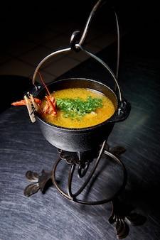 Hete soep met rivierkreeft die in ketel wordt gekookt.