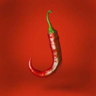 Hete spaanse peperpeper die over rood oppervlakte drijft