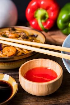 Hete spaanse pepersaus in houten kom met udonnoedels met garnalen op houten lijst