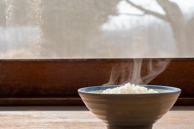 Hete stoomrijst in witte ceramische kom met rook op houten bureaulijst.
