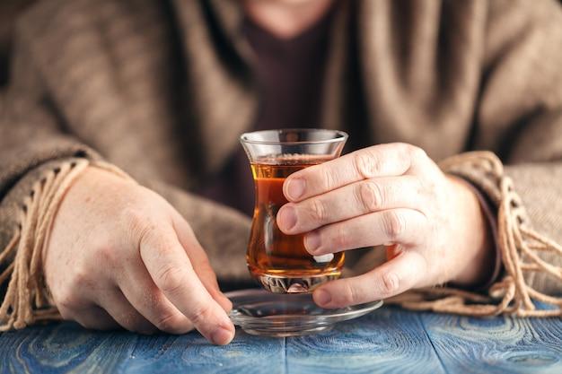 Hete thee in glazen beker in mannelijke handen