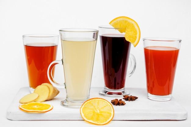 Hete thee in glazen mok met citroen, honing en kruiden op wit. gezonde drank. detailopname.