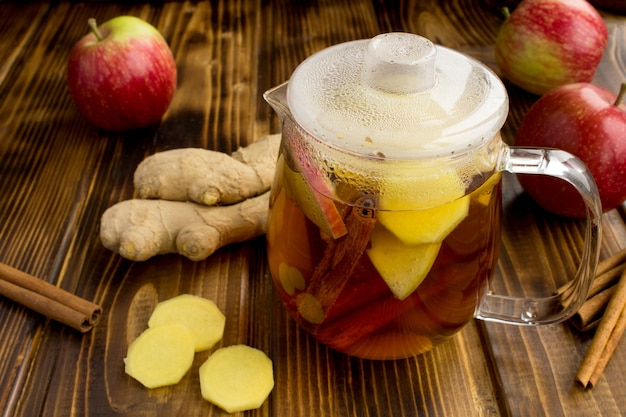 Hete thee met appels, kaneel en gember in de glazen theepot op de bruine houten achtergrond. gezond drankje.