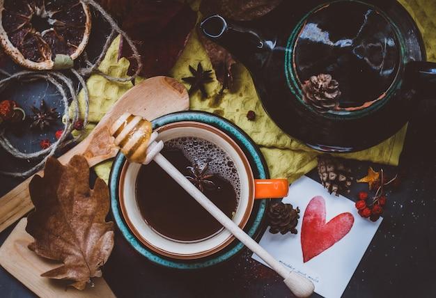 Hete thee met honing en kaneel in een oranje beker herfstsfeer op een donkere ondergrond