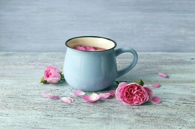 Hete thee met rozenblaadjes in een grote kop, verse bloemen op een houten tafel