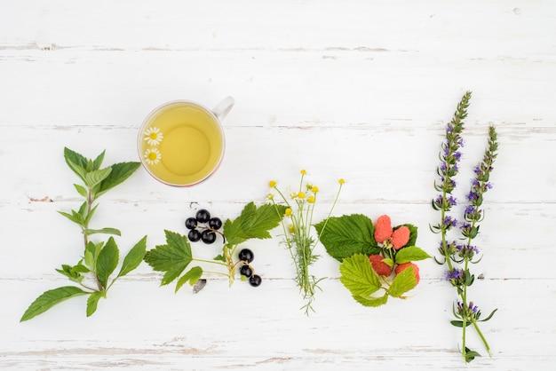 Hete thee op een houten witte achtergrond, de ingrediënten voor de bereiding van natuurlijke kruidenthee