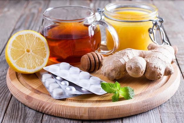 Hete thee voor verkoudheid geneeskunde en honing op houten tafel