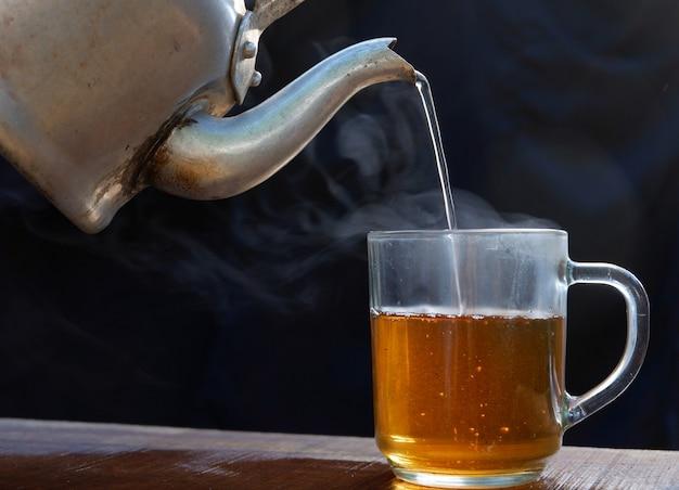 Hete theekop heeft hete stoom met waterkoker. geplaatst op een oude houten tafel, zwarte achtergrond