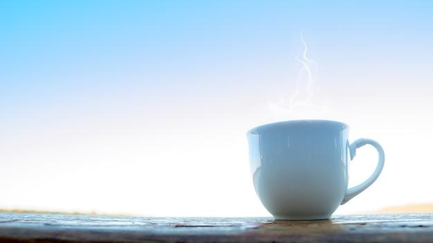 Hete theekopbovenkant op houten met zonsondergangtijd.