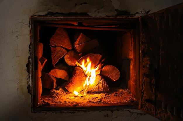 Hete vlam en brandhout in oude kachel in het dorp.