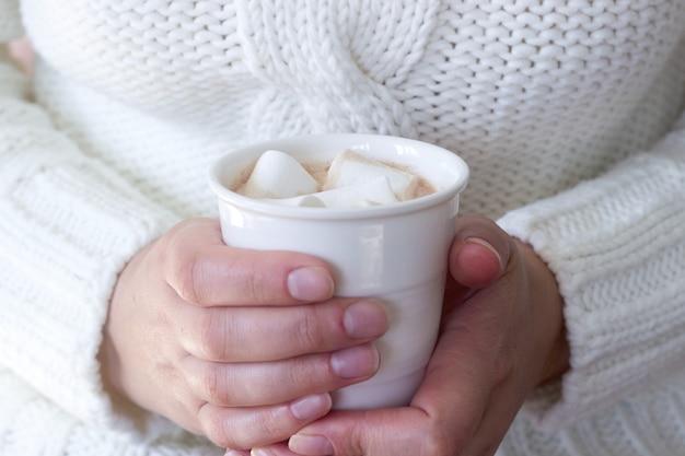 Hete zelfgemaakte cacao met marshmallow in de handen van een vrouw.