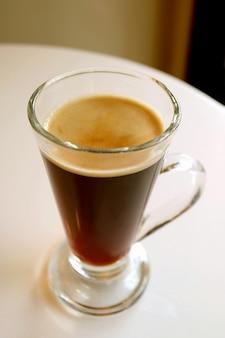 Hete zwarte koffie in een transparant glas geserveerd op witte ronde tafel