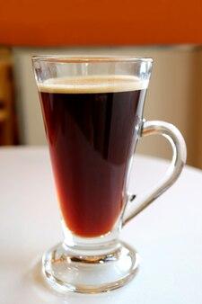Hete zwarte koffie in een transparant glas geserveerd op witte tafel