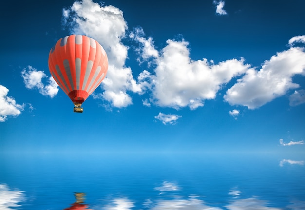 Heteluchtballon in blauwe lucht boven het wateroppervlak
