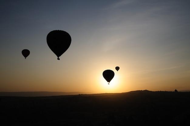 Heteluchtballon silhouet vliegen ochtend goreme landschap cappadocië turkije