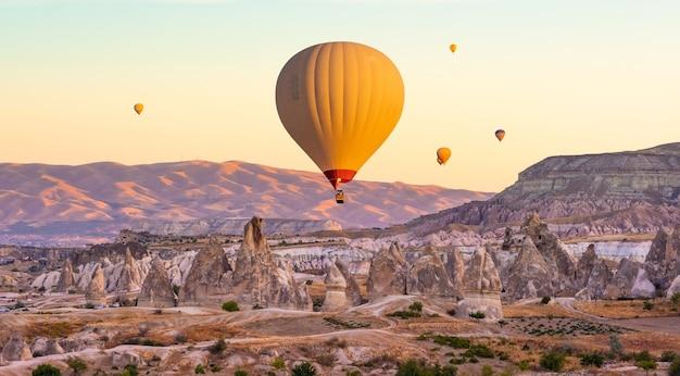 Heteluchtballonnen vliegen op de avondrood in cappadocië, turkije
