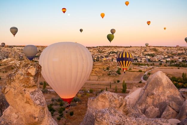 Heteluchtballonnen zweven over bergen in cappadocië, turkije
