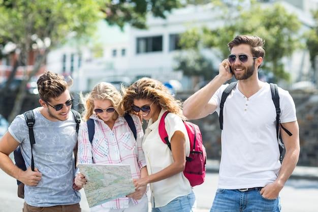 Heupmens op telefoongesprek en vrienden die kaart in openlucht controleren