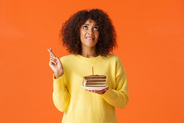 Heupportret hoopvol schattig dromerig, feestvarken met afro-kapsel, bijtende lip en wenswens die uitkomt, hemel biddend opzoeken, veel geluk met de vingers, kaars uitblazen op verjaardagstaart