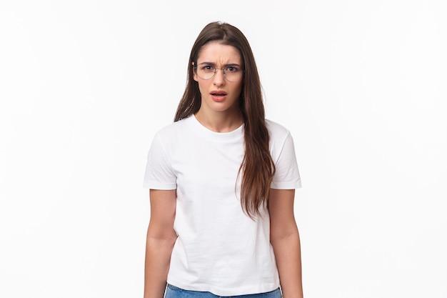 Heupportret van gefrustreerde en geschokte jonge vrouwelijke collega hoort vreemde bekentenis