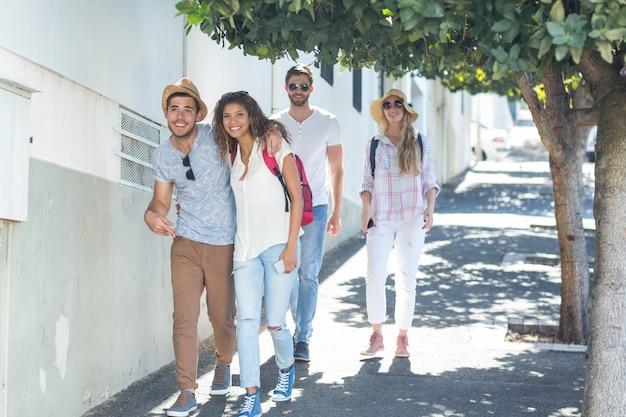 Heupvrienden die op de straat lopen en bij de camera glimlachen