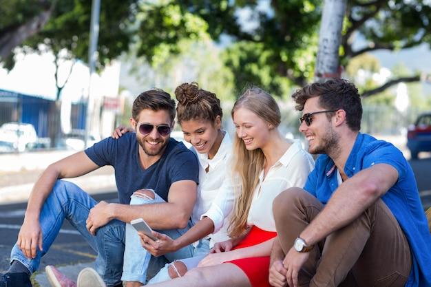 Heupvrienden die smartphone bekijken en op stoep in de stad zitten