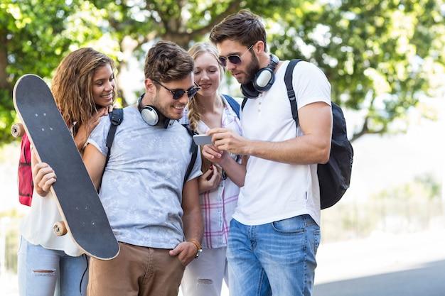 Heupvrienden die smartphone in openlucht bekijken