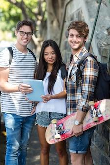 Heupvrienden met tablet die bij de camera op de straat glimlachen