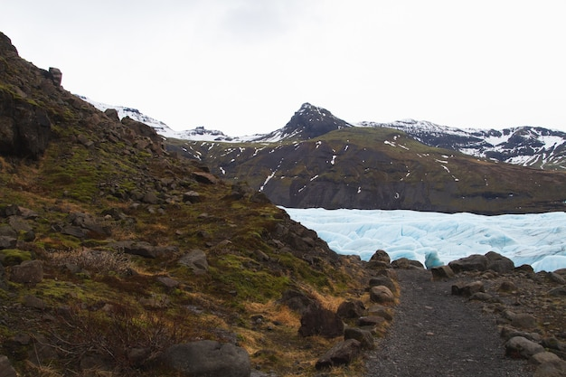 Heuvels bedekt met sneeuw en gras omgeven door een bevroren meer in vatnajokull national park