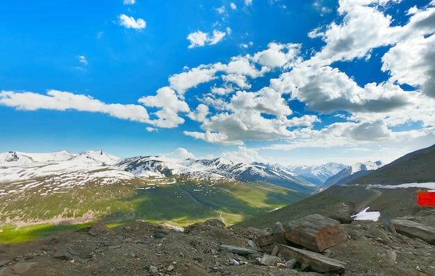 Heuvels bedekt met sneeuw en groene weiden