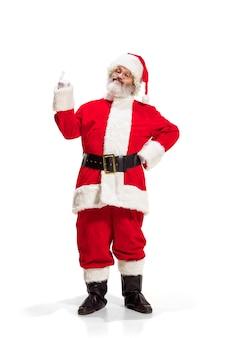 Hey hallo. holly jolly x mas feestelijke noel. volledige lengte van grappige gelukkige kerstman in hoofddeksels, kostuum, zwarte band, witte handschoenen, golven met armpalm staande in de studio op witte achtergrond