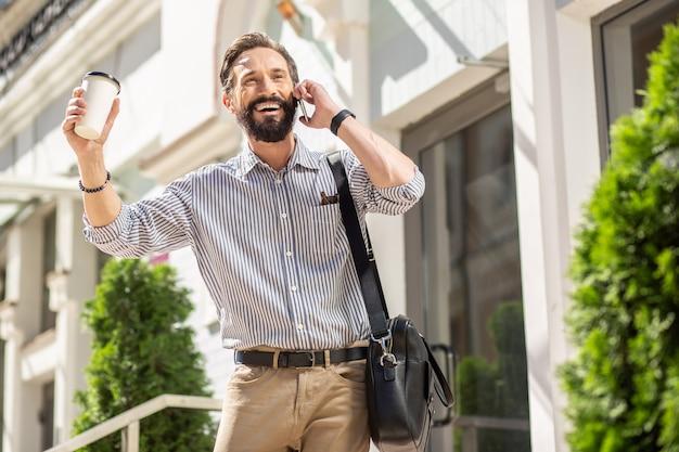 Hey jij. vrolijke man praten over de telefoon terwijl hij in de buurt van zijn huis staat
