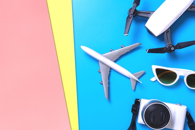 Hi tech reisgadget en accessoires op blauwe en roze gele achtergrond