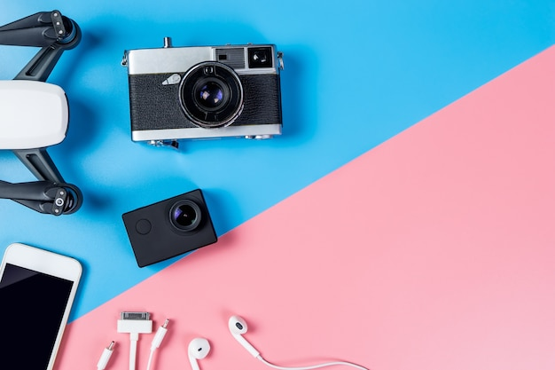 Hi-tech reismagentoestel en toebehoren op blauwe en roze exemplaarruimte