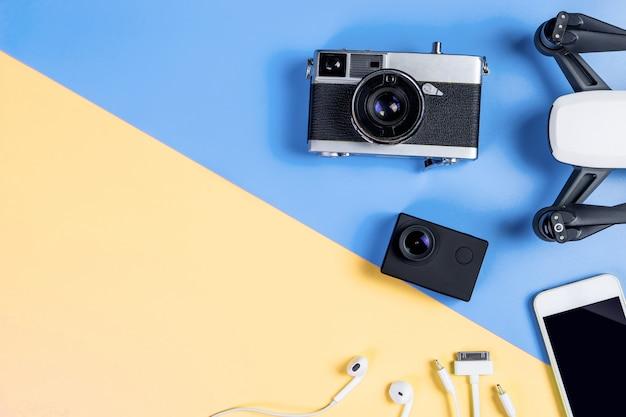 Hi tech reizen gadget en accessoires op blauwe en gele kopie ruimte bovenaanzicht plat lag
